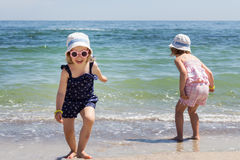 美丽的小女孩(姐妹)在海滩跑 免版税库存图片
