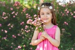 美丽的小女孩画象有玫瑰的开花 免版税库存图片