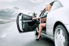美丽的小姐出来了frome她的在路的汽车 免版税库存图片