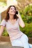 美丽的小姐坐户外和谈话在手机 图库摄影