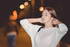 美丽的小姐画象在城市街道上的夜,平衡点燃bokeh背景 免版税库存照片