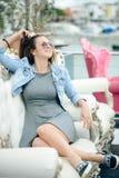 美丽的小姐画象坐在典雅的扶手椅子的太阳镜的 免版税库存照片