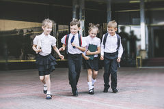 美丽的小学生活跃和愉快在背景  图库摄影