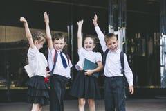 美丽的小学生活跃和愉快在背景  免版税库存图片