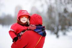 美丽的小孩和他的母亲画象在多雪的公园 库存图片