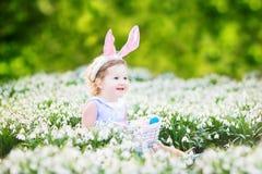 美丽的小孩女孩复活节彩蛋在第一春天开花 免版税库存图片