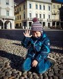 美丽的小男孩坐地面 免版税库存照片