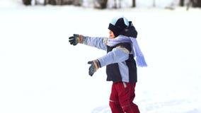 美丽的小男孩获得使用的乐趣在雪 影视素材