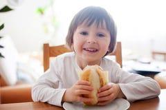 美丽的小男孩,在家吃三明治,在的菜 库存图片