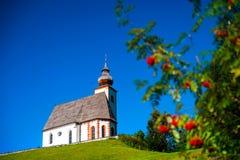 美丽的小的教会在阿尔卑斯 晴天,在h的绿草 图库摄影