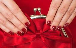 美丽的小红色女性钱包在手上 免版税库存图片