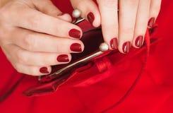 美丽的小红色女性钱包在手上 免版税库存照片