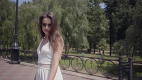 美丽的少女佩带的太阳镜和走一件长的白色夏天时尚的礼服户外 休闲俏丽 影视素材