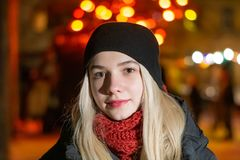 美丽的少女在摆在反对夜光背景的晚上  黑帽会议的金发碧眼的女人微笑着 免版税库存图片