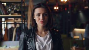 美丽的少女画象皮夹克的在与严肃的面孔的咖啡馆 股票录像