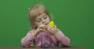 美丽的少女紧压柠檬汁并且喝它与在面孔的一副鬼脸 影视素材