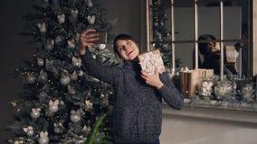美丽的少女采取selfie使用在圣诞节身分的智能手机在装饰的壁炉和新年附近 股票视频