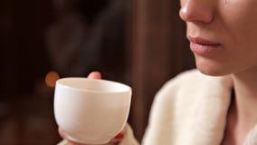 美丽的少女饮用的茶在温泉治疗以后的放松屋子 r 股票录像