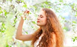 美丽的少妇享用气味在庭院的春天花 免版税图库摄影