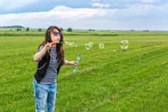 美丽的少妇做吹的泡影 免版税图库摄影