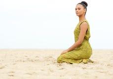 美丽的少妇单独坐沙子在海滩 免版税库存照片