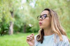 美丽的少妇吹的蒲公英花画象  图库摄影