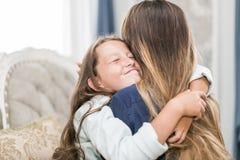 美丽的少妇和她迷人的矮小的女儿拥抱并且微笑着 免版税库存照片