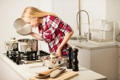 美丽的少妇在厨房烹调一顿可口膳食 图库摄影
