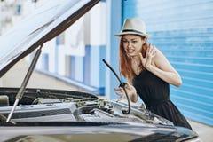 美丽的少妇在城市,情感修理一辆汽车 免版税库存照片