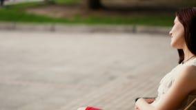 美丽的少妇在夏天公园神奇微笑,坐一条长凳 户外妇女的纵向 影视素材