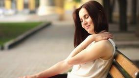美丽的少妇在夏天公园神奇微笑,坐一条长凳 户外妇女的纵向 股票录像