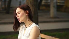 美丽的少妇在夏天公园神奇微笑,坐一条长凳 户外妇女的纵向 股票视频