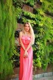 美丽的少妇在夏天绿色开花的庭院里 免版税图库摄影