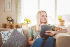 美丽的少妇在家坐沙发,举行数字式t 免版税库存照片