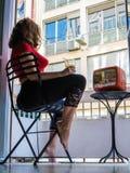 美丽的少妇在家给坐在阳台的一把椅子和看电视穿衣 库存图片