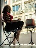 美丽的少妇在家给坐在阳台的一把椅子和看电视穿衣 免版税库存图片