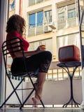 美丽的少妇在家给坐在阳台的一把椅子和看电视穿衣 免版税图库摄影
