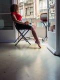 美丽的少妇在家给坐在阳台的一把椅子和看电视穿衣 免版税库存照片