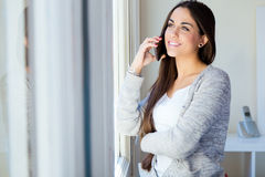 美丽的少妇在家谈话在电话 免版税库存照片