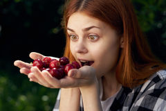 美丽的少妇在庭院拿着一棵樱桃 库存图片