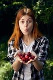 美丽的少妇在庭院拿着一棵樱桃 免版税库存照片