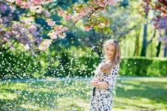 美丽的少妇在开花的春天公园 免版税库存照片