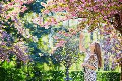 美丽的少妇在开花的春天公园 免版税库存图片