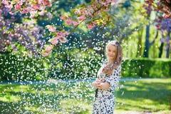 美丽的少妇在开花的春天公园 免版税图库摄影