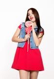 美丽的少妇在拿着棒棒糖,演播室射击的一件红色礼服穿戴了 免版税库存图片
