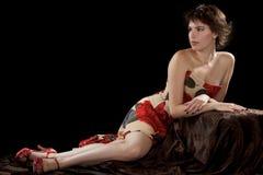 美丽的少妇在无背带的礼服斜倚 免版税库存照片