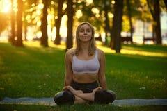 美丽的少妇在日落的公园实践瑜伽asana Padmasana -莲花姿势 免版税库存图片