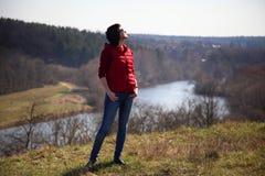 美丽的少妇在春天太阳的光芒沐浴在小山的在河上 摆在为在natur的一台照相机的美丽的妇女 免版税图库摄影