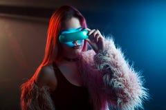 美丽的少妇在未来派玻璃虚拟现实,计算机国际庞克样式,霓虹灯中 免版税库存照片