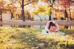 美丽的少妇在秋天公园实践瑜伽asana 免版税库存照片